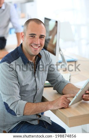 Young smiling man in training class using digital tablet