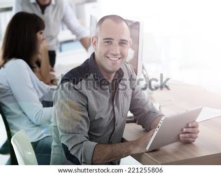 Young smiling man in training class using digital tablet - stock photo
