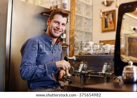 Young smiling man is making coffee with a coffee machine. - stock photo