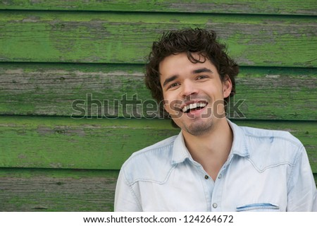 Young smiling man leaning against a green wooden wall outdoors. He is looking at camera. Copy space possibility - stock photo