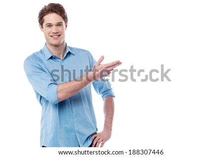 Young smiling man presenting copy space area - stock photo