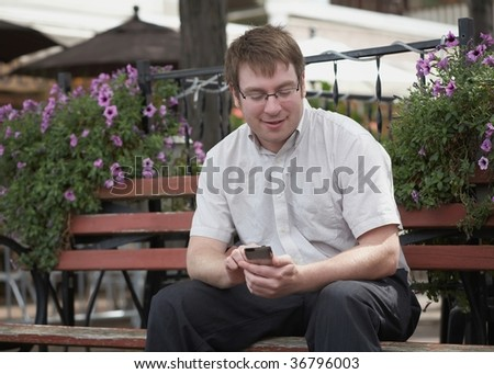 Young smiling man sending text message with modern mobile phone - stock photo