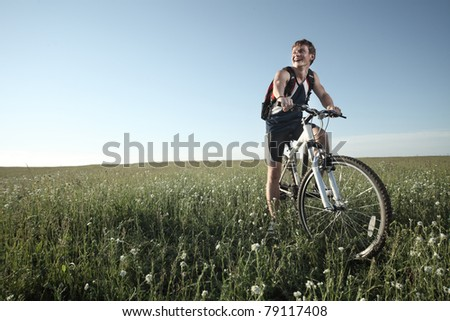 Young smiling man standing on meadow with bicycle - stock photo