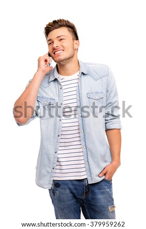Young smiling man talking on the mobile phone and looking away. Isolated on white. - stock photo