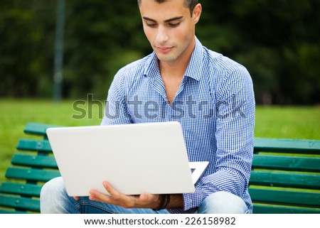 Young smiling man using a laptop computer outdoors