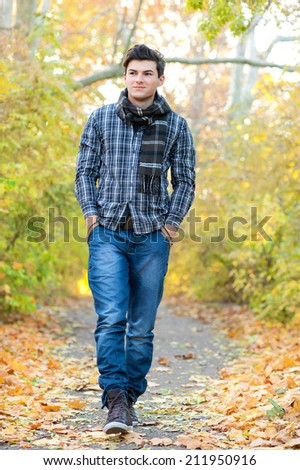Young smiling man walking in autumn park. - stock photo