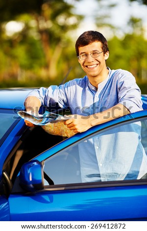 Young smiling man wearing glasses with road map leaning on blue car with open door - stock photo