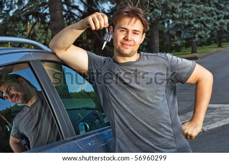 Young smiling man with keys of new car. - stock photo