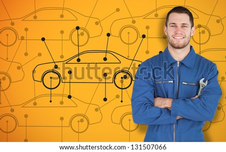 Young smiling mechanic standing in front of cars background while looking at camera - stock photo