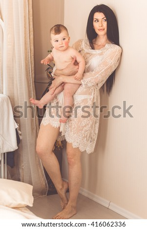 Young smiling mother is holding her naked baby boy by hands