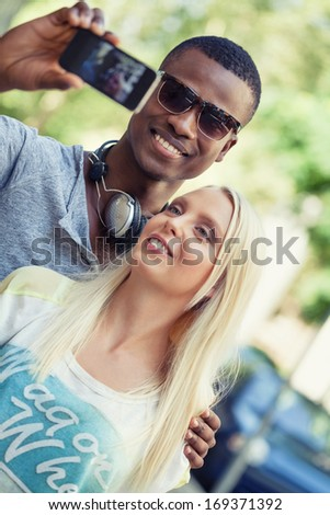 young smiling multiracial couple taking foto by smartphone outdoor in summer