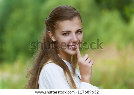 Young smiling nice woman puts finger to her lips, against background of autumn park.