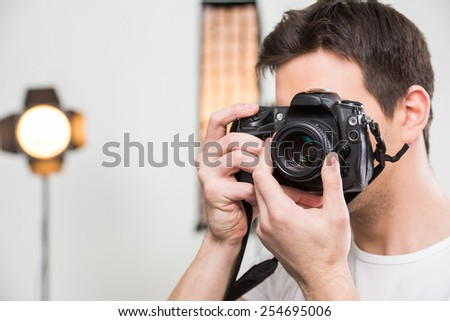 Young smiling photographer with camera in professionally equipped studio. Close-up.