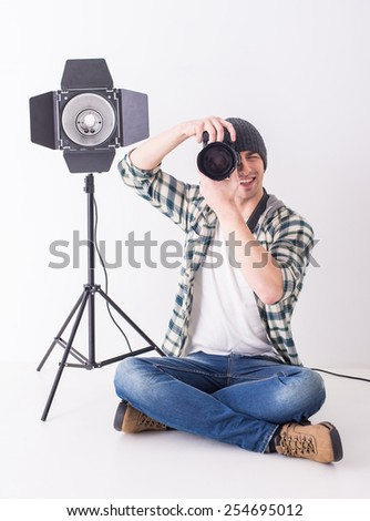 Young smiling photographer with camera in professionally equipped studio is sitting on the floor.