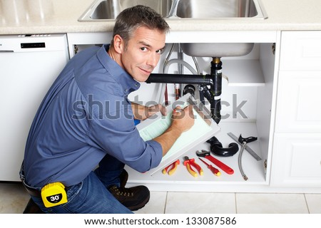 Young smiling plumber fixing a sink in the kitchen.