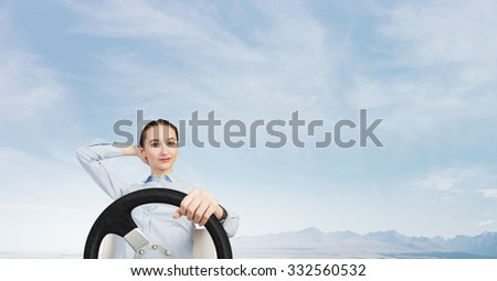 Young smiling pretty woman driving steering wheel - stock photo