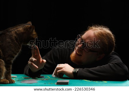 Young smiling red-haired bearded man in glasses playing poker with tabby cat sitting at gaming table on black background - stock photo