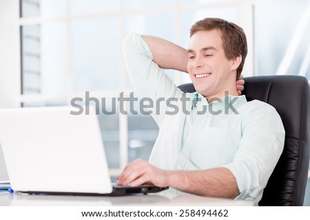 Young smiling relaxed businessman working with laptop and sitting at his black leather office chair. Office interior with window - stock photo