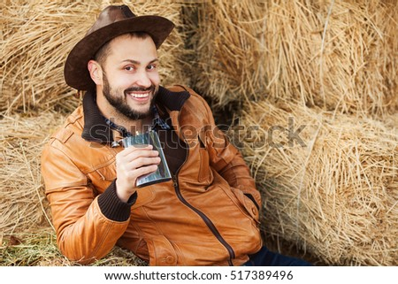 Young smiling relaxed cowboy in brown leather jacket laying on straw bales and drinking whiskey from metal flask. Copy-space. Close up. Outdoor shot
