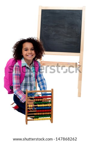 Young smiling school kid in classroom environment - stock photo