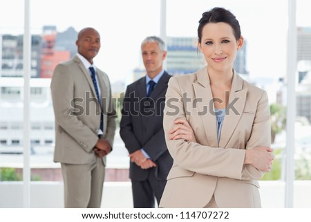 Young smiling secretary crossing her arms in front of two executives - stock photo