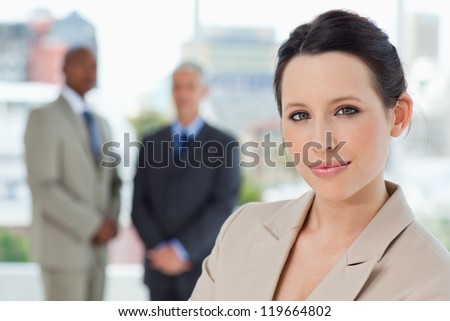 Young smiling secretary standing in front of two businessmen in a relaxed way - stock photo
