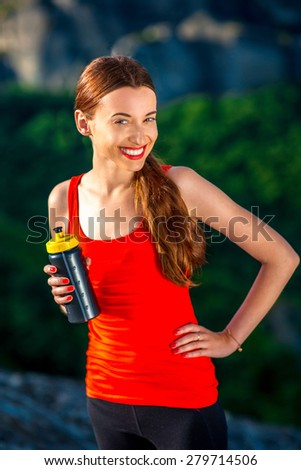 Young smiling sport woman with drink bottle in the mountains - stock photo