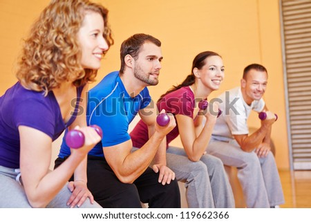 Young smiling sports group exercising with dumbbells in a gym