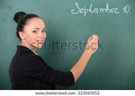 Young smiling student or teacher at the blackboard