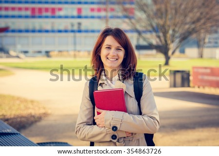 Young smiling student professional outdoors  holding a red book.University.Smiling young student girl holding a book on a university background .Young smiling student outdoors Life style.City.Student.