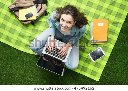 Young smiling student relaxing outdoors, she is sitting on the grass and using a laptop, summer camp concept