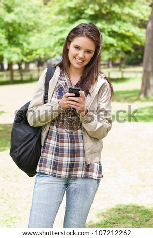 Young smiling student using a smartphone in a park - stock photo