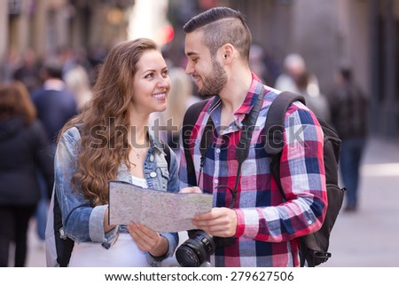Young smiling travelers going sightseeing with camera through square of European city - stock photo