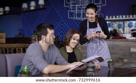 Young smiling waiter taking order from two young people sitting at table and using menu.