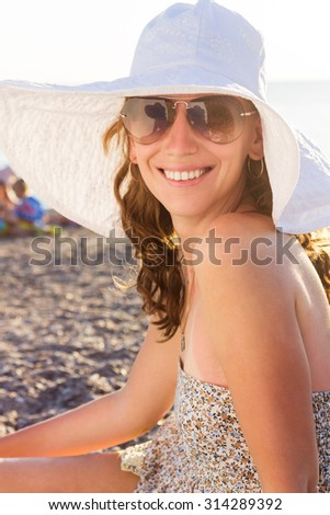 Young smiling woman at the beach near sea. Pretty caucasian girl in white hat looks straight into camera - stock photo