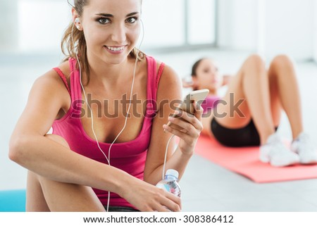 Young smiling woman at the gym having a break and listening to music using a smart phone and earphones, fitness and youth concept - stock photo