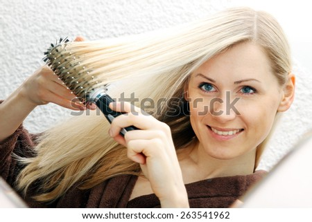 young smiling woman brushing her long blond hair - stock photo