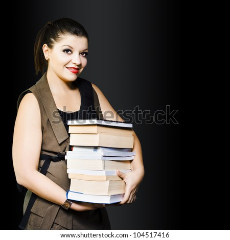 Young smiling woman carrying library books in a education and studying concept on dark background - stock photo