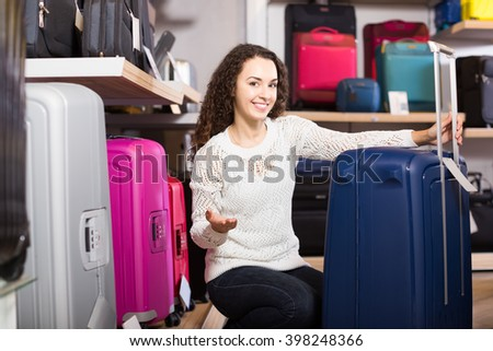 Young smiling woman choosing travel suitcase in haberdashery shop