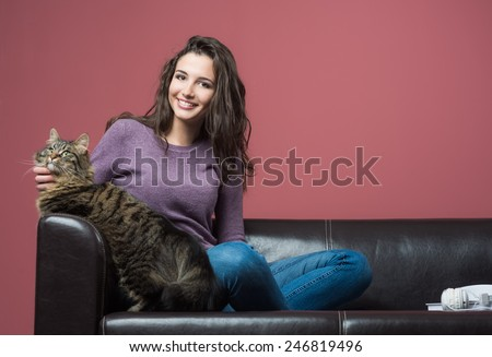 Young smiling woman cuddling her long hair beautiful cat - stock photo