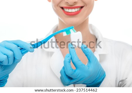 Young smiling woman doctor in uniform brushing artificial tooth on white background - stock photo