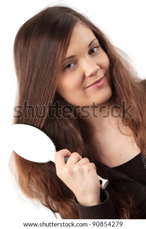 Young smiling woman doing her long hair - stock photo