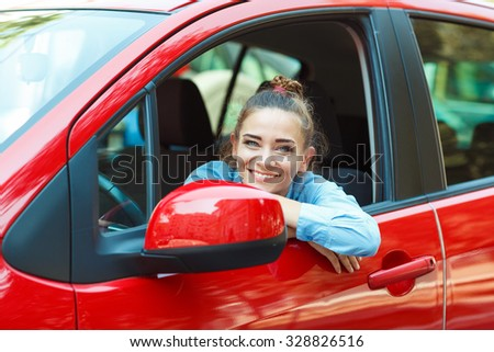Young smiling woman driving her car - stock photo