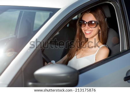Young smiling woman driving her new car - stock photo