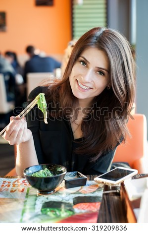 Young smiling woman eating japanese seaweed salad (Chuka) in a sushi restaurant. - stock photo
