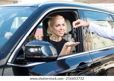 Young smiling woman getting keys of a new car. Concept for car rental  - stock photo