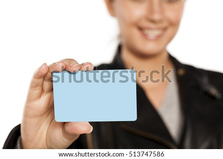 young smiling woman holding a plastic credit card on a white background