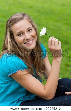 Young smiling woman holding a white flower while sitting down in the countryside - stock photo