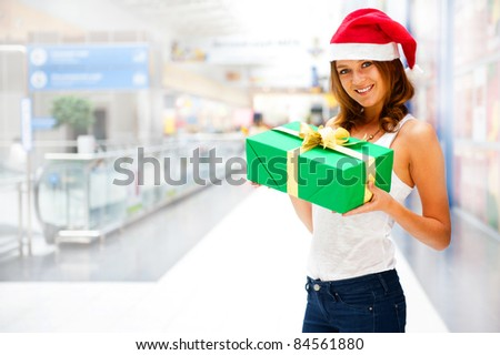 Young smiling woman holding gift standing at shopping mall wearing Santa Claus hat