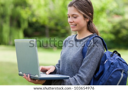 Young smiling woman holding her laptop while standing in a park with hair tied